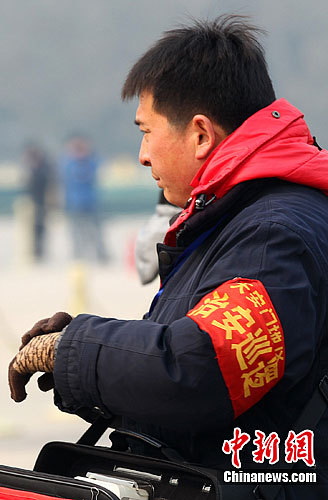 """2月29日,戴着""""天安门地区治安巡逻""""的男子在天安门广场上执勤。中新社记者 泱波 摄"""