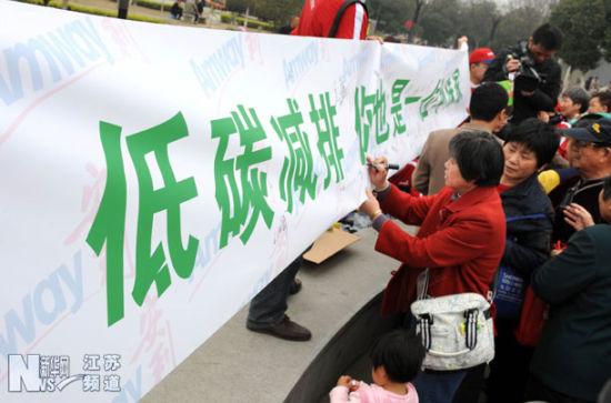 """3月29日,市民们在""""低碳减排""""条幅上签名。"""