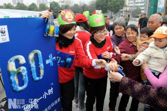 3月29日,志愿者向准备参加熄灯1小时活动的市民发放手动发电的小电筒。