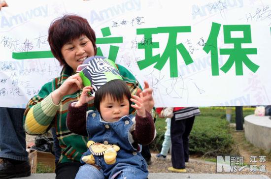3月29日,参加活动的市民给孩子戴上志愿者发放的环保宣传帽。