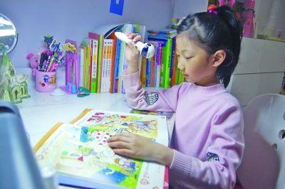 小庭好在用点读机学习英语。