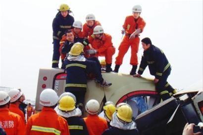 救援人员将伤者从倾倒的大巴内抬出。