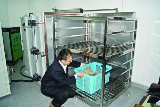 """苏州博物馆工作人员把文物放进消毒机""""过堂""""。"""