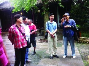 纪纲(右一)在寄畅园内和游客讲景