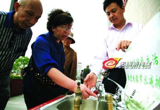 """昨天,我市启动第21个""""全国城市节约用水宣传周""""活动。图为市民在活动现场了解节水水龙头使用原理。"""