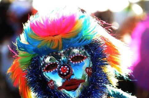巴西里约热内卢的狂欢节,一个戴面具的狂欢者加入了班达亚齐街头乐队游行。