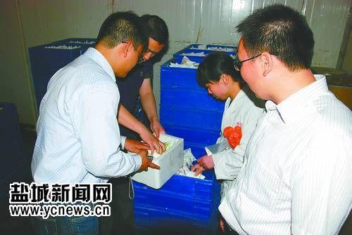 质检工作人员对乳制品进行抽检。