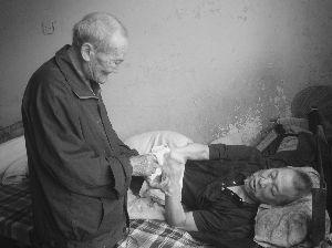 徐松德为躺在床上的儿子徐保银擦手