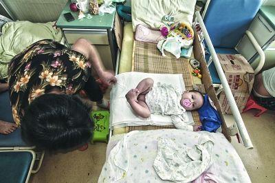 宝宝被放在床上,口中含的奶嘴是他最喜欢的安慰玩具。