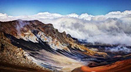 在哈来亚咔拉国家公园透着火山山顶的云层看日出