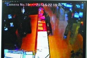 视频截图:劫匪在用铁榔头砸柜台玻璃