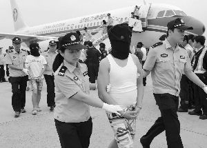 犯罪嫌疑人戴着头套被押下飞机