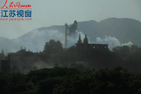 镇江丁台村白青山水库附近山头冒出浓烟和灰尘。