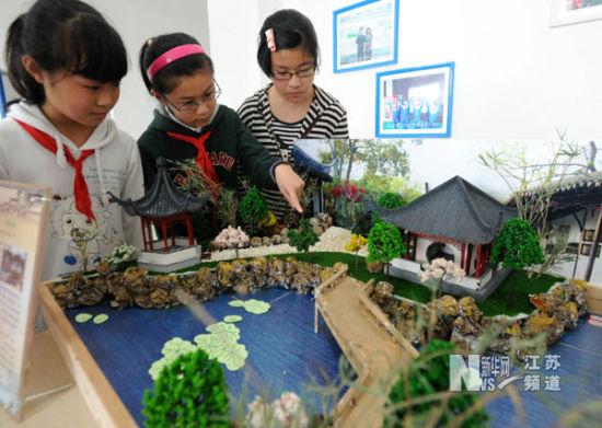 """5月24日,几名学生在少儿科技节成果展上观看""""拙政园""""建筑模型。"""