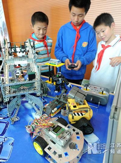 5月24日,苏州新庄小学的一名学生(中)为参观者进行机器人表演。