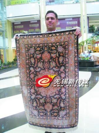 波斯波利斯地毯总经理何飞(中文名)正在展示一条售价7万元的波斯毯。