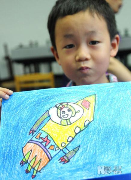 """6月18日,一名苏州市彩香幼儿园的小朋友展示自己描绘的""""神九""""载人飞船。"""