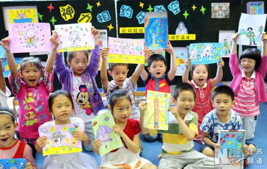 """6月18日,苏州市彩香幼儿园的孩子们展示他们创作的""""神九""""飞天主题绘画。"""