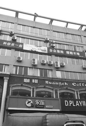 男子骑在楼顶的横梁上非常危险   现代快报记者   王晓宇 摄