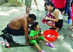 记者找到小女孩时,男子正带着她在中央路上乞讨 现代快报 (微博)记者 施向辉 摄