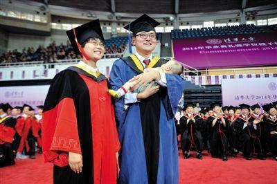 清华大学的博士研究生陈程(左)和丈夫仲晓波(右)怀抱着三个月大的女儿参加毕业典礼。