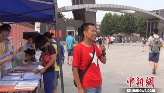高三毕业生李嘉诚(中)拿着话筒向路过学生们推介笔记. 王帅 摄