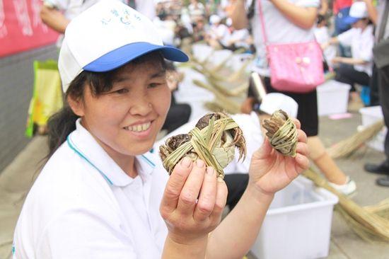 蟹农展示扎好的螃蟹